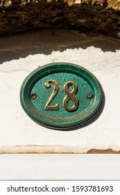 House number 28 on an oval metal sign on a White House wall worn & weathered with cobwebs