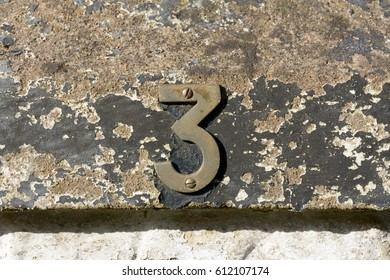House number 3 sign on wall with peeling paint