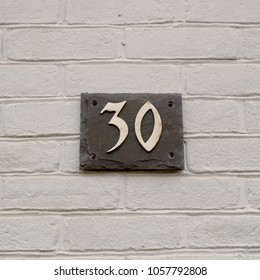House number 30 sign fixed to brick wall
