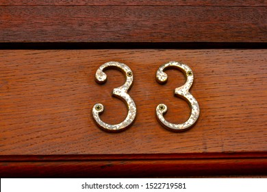 House number 33 on a natural grained wooden front door
