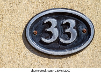 House number 33 on an oblong plaque on a plaster wall