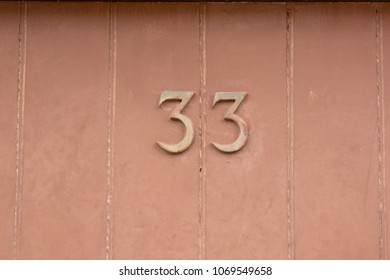 House number 33 sign on door painted brown