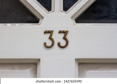 House number 33 with the thirty-three in metal digits on a white wooden front door