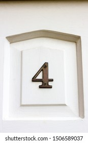 House number 4 on a white wooden front door