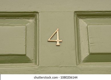 House number 4 sign on green painted door