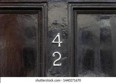 House number 42 with the forty-two in silver metal digits on an old black painted wooden front door with panels