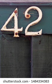 House number 42 on a black wooden fence