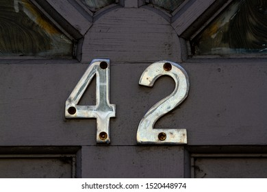 House number 42 in shiny metal digits on a black wooden front door
