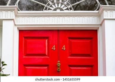 House number 44 with the forty-four In bronze metal digits on a bright red wooden front door with ornate door handle with white door frame