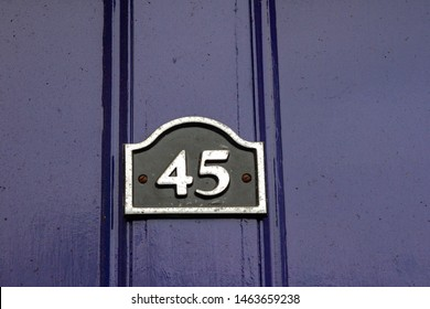 House number 45 with the forty five on a black plaque with silver border on a dark blue or purple wooden front door