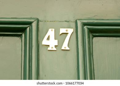House number 47 sign on green painted door
