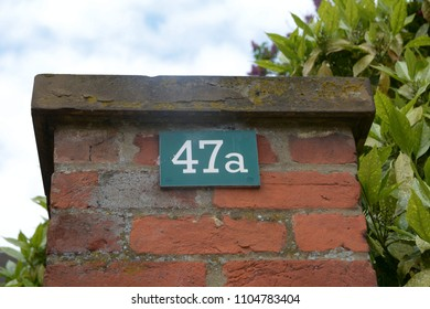 House number 47A sign on gate post