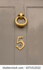 House number 5 sign on green door with brass door knocker