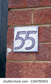 House number 55 sign on red brick wall