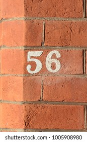 House number 56 sign painted on wall
