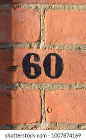 House number 60 sign painted black on wall