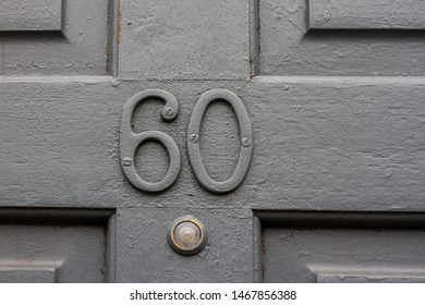 House number 60 with the sixty in painted metal numbers on a grey wooden front door