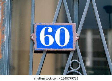 House number 60 White on blue on an old metal gate of a authentic Franch house