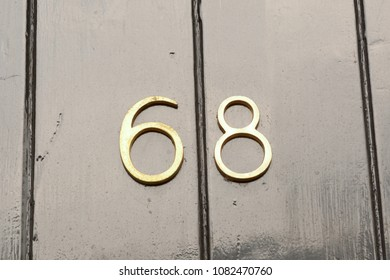 House number 68 sign on black painted wooden door