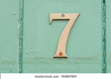 House number 7 sign on green painted door
