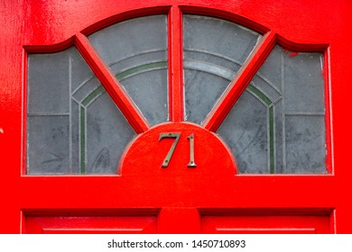 House number 71 with the seventy-one in bronze metal digits on a bright red wooden front door with glass