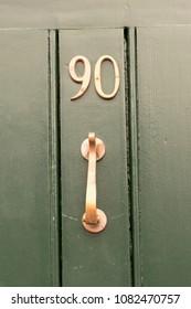 House number 90 sign on green door with brass door knocker