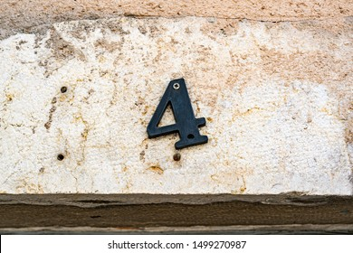 House number four (4) dangling on one screw against a weathered wall