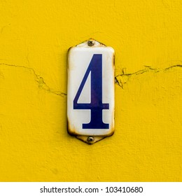 house number four on a rusty enameled plate against a bright yellow painted wall