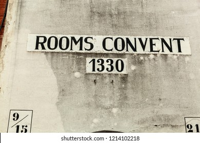 House number nine fifteen twenty-one 9 15 21 1330 painted black on white render in times new roman type on weather white background in Brugges Belgium Rooms Convent