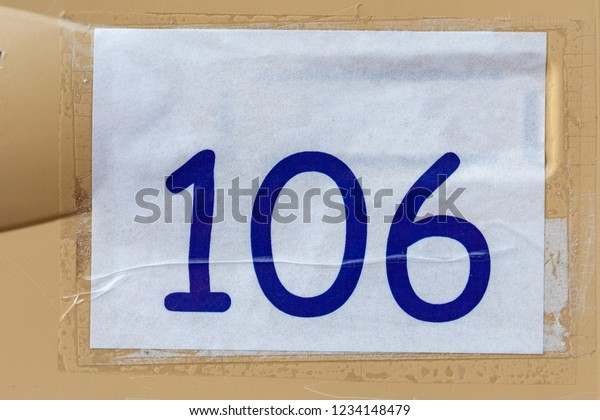 a3caa5aeb7a8 House number one hundred six 106 computer printed in large blue comic sans  style font on