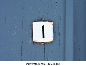 House Number One sign on blue painted wooden door