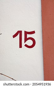 A house number plaque, showing the number fifteen (15)