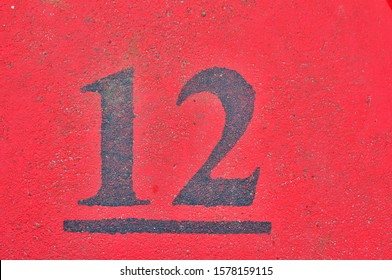 A house number plaque, showing the number twelve (12)