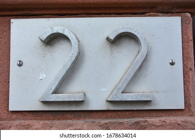 A house number plaque, showing the number twenty two (22)