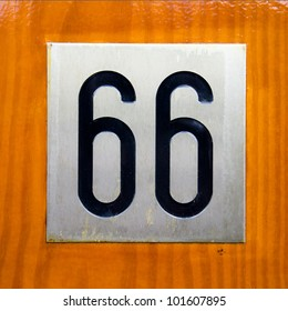 house number sixty-six. Black font on metal plate on clear lacquered wooden background