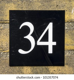 house number thirty-four. White font on black plastic
