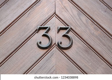 House number thirty-three 33 in designer font in cast black painted metal, weathered or tarnished from Belgium
