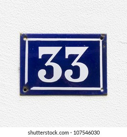 house number thirty-three, white lettering on a blue enameled plate