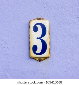 house number three on a rusty enameled plate against a light violet painted wall
