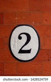 House number two painted in a white and black oval on a red brick wall with the 2 in black