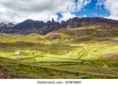 House on a background of mountains under clouds in Iceland
