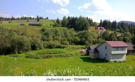 House on bright green lawn in rural landscape on a summer day