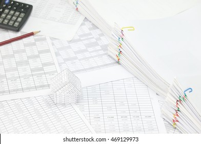 House on finance account have blur brown pencil with black calculator and overload of paperwork with colorful paperclip on right as background. Business and finance concepts successful photography.