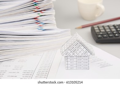 House on finance account have blur pile overload document of report and receipt with colorful paperclip and calculator with pencil and cup of coffee as background. Business and finance concept photo.