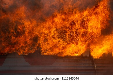 House is on fire. Open flame. Firefighters fight with fire