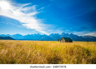 House on a Golden Grass Prairie against the Grand Teton Mountains.  Near Moulton Barns.  Grand Teton National Park, Jackson Hole, Wyoming, USA.