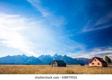 House on a Golden Grass Prairie against the Grand Teton Mountains.  Near Moulton Barns.  Grand Teton National Park, Jackson Hole, Wyoming, USA.