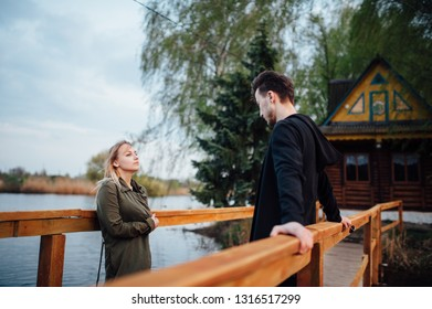 a house on an island in the middle of a lake on the background of which a lovers couple kisses