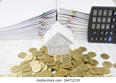 House on stack silver and gold coins with pile of paperwork as background. Stack of paperwork is high as work hard. Business and finance concepts rich and successful photography.