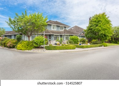 House on a sunny day with front yard, trimmed lawn.